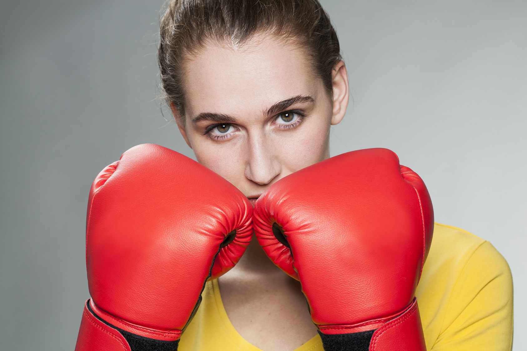 proud young woman protecting herself with boxing gloves for female protection concept